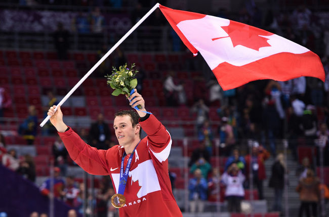 Jonathan Toews of the Canadian Men's Olympic team proudly waves the flag.
