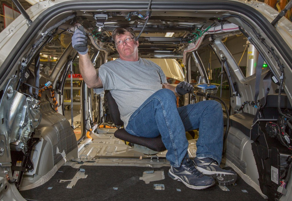 GM assembly team member Jim Clarke uses connects wire harnesses to a 2014 Chevrolet Traverse at GM's Lansing Plant.